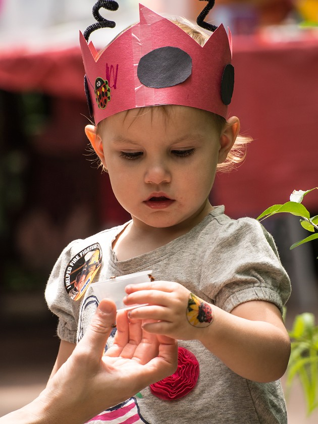 A child enjoys viewing a ladybug while dressed as a ladybug. - Photo by Carl Shortt - CARL SHORTT