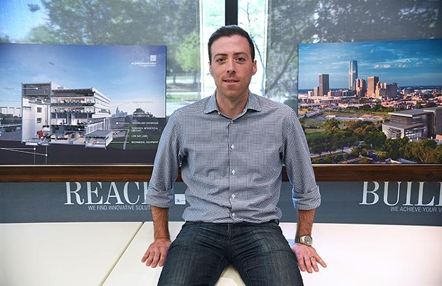 Cory Baitz, an architect with Miles Associates and is also on Oklahoma City's Downtown Design Review Committee, poses with artist renderings of the G.E. Global Research Center now under construction accross the street from his office.  mh