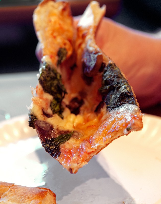 A customer folds his big floppy slice of Fungus Among Us for eating, at Empire Slice House. (Mark Hancock)