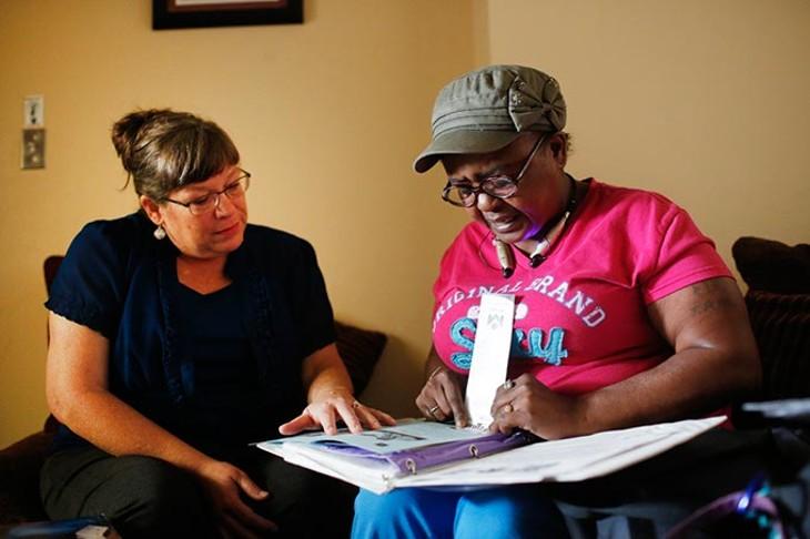 Zoe Anderson reads for Blair Lanning, volunteer coordinator at Opportunities Industrialization Center, in Oklahoma City, Wednesday, Aug. 26, 2015. - GARETT FISBECK