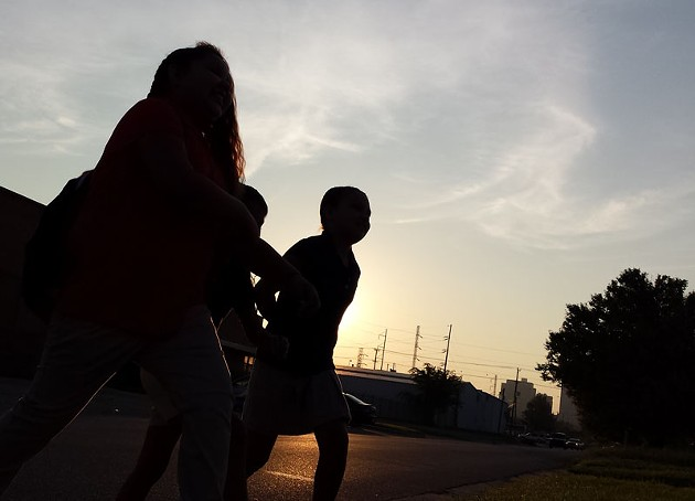 Students walk to the bus stop on the first day of class in the early morning hours on Aug. 4, 2014. - BEN FELDER