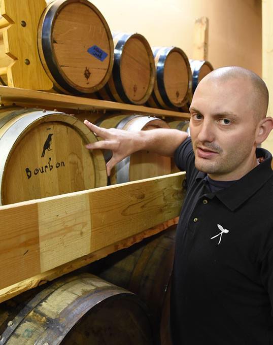 Jarrett Janko with kegs of Bourbon at Scissortail Distillery. (Mark Hancock)
