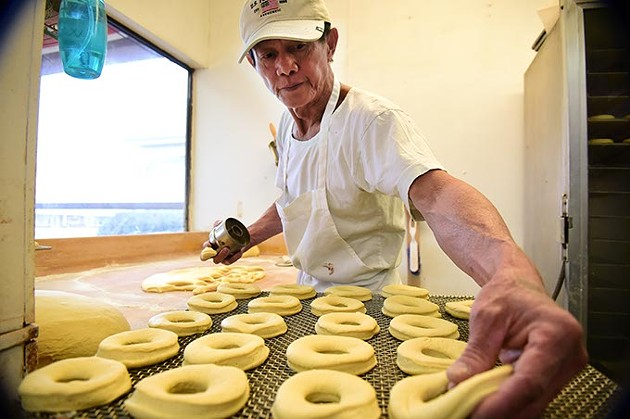 Sok San has been the baker at North May Donuts & Kolaches for over 5 years, shown forming donut dough on the recent busy Christmas Eve morning.  mh