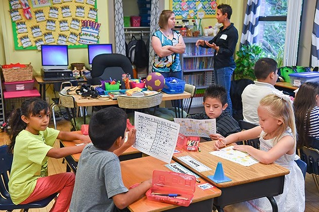 Left to Right, Lori Zehnder, 3rd grade teacher at Linwood Elementary School, chats with Melissa O'Neil, Donors Choose program with Foundation for OKCPS, in background of classroom using some of the donated supplies, 8-27-15. - MARK HANCOCK