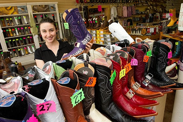 Gloria Carreon holds up a purple pointed toe boot at El Rancho.Photo/Shannon Cornman - SHANNON CORNMAN