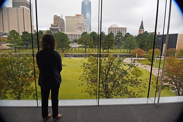 Mary Anne Eckstein at the new, large Oklahoma City National Memorial viewing window, from inside the Memorial Museum where she serves as Director of Media, 10-23-15. - MARK HANCOCK