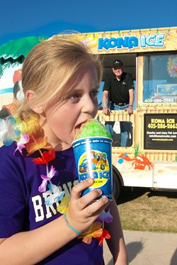 Kate Thomas chomps into a  King Kona while visiting the Kona Ice truck at a recent sporting event.  Kona Ice owner Charles Love watches from his truck.  mh