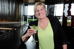 Margaret Holloway poses for a photo with her signature drink, The Gecko Fizz, at Cafe 501 in Oklahoma City, Tuesday, May 26, 2015. - GARETT FISBECK