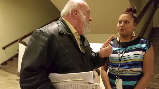"""Carrel Wilson expressed his support for the """"Redskin"""" mascot with a volunteer during a forum on Tuesday. - BEN FELDER"""