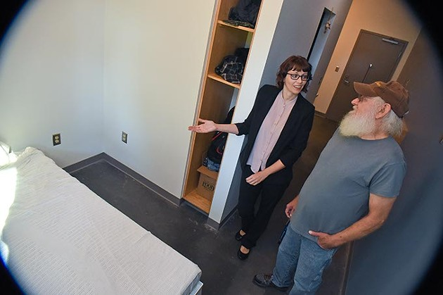 Larry Murray and Kim Woods, deputy director of The Homeless Alliance, discuss the benifits of his new home in the West Town Apartments, on the property of the WestTown Homeless Resource Campus in Oklahoma City, 9-21-15. - MARK HANCOCK