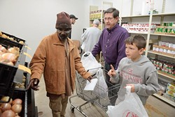 Elvis Howard shops for groceries with assistance from volunteers Les Wright and his grandson, Kaden Jacobs, 11, at Love Link Ministries.(Garett Fisbeck)