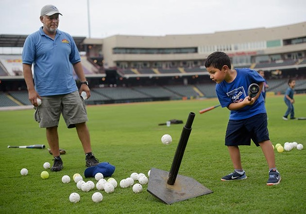 Emiliano Hernandez, 6, hits a ball off a tee as his father, Jorge, looks on during an OKC Dodgers Clinic in conjunction with Supermercados Morelos, Friday, July 28, 2017. - GARETT FISBECK