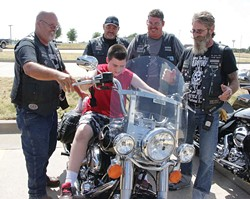 Members of the Survivors Clean and Sober Motorcycle Club give McCarty Center patient Xaviar Smith a taste of what riding a Harley is like during last year's Ride for Recovery. The Ride for Recovery poker run benefits Camp ClapHans, a summer camp program of the J. D. McCarty Center. - PHOTO BY SHARLA BARDIN