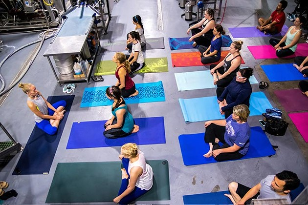 Surrounded by brewing equipment, Instructor Brooke Larson, left, leads a class of Beer Yoga, at Coop Ale Works in southwest Oklahoma City, 10-15-2016. - MARK HANCOCK