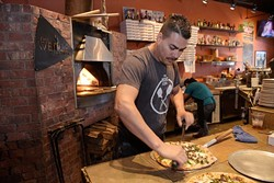 Jesus Cortez cuts a pizza at The Wedge, Monday, Oct. 24, 2016.  Cortez has worked at The Wedge for 8 years. - GARETT FISBECK