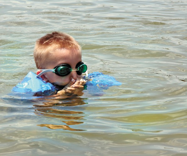 young boy plugs his nose while learning to swim - BIGSTOCK