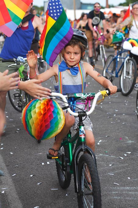A young child rides their bike with the Bike Brigade during the Pride Parade on Sunday, June 25, 2017. (Cara Johnson).