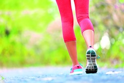Woman with athletic legs on jog or run on trail in forest in healthy lifestyle concept with close up on running shoes. Female athlete jogging and training outdoors. - BIGSTOCK