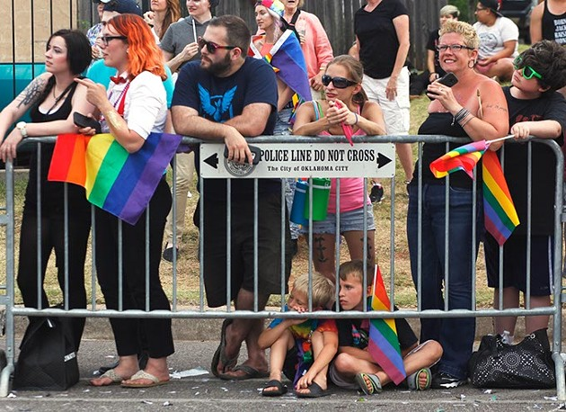 Two young boys sit on the ground watching the Pride Parade on Sunday, June 25, 2017. (Cara Johnson).