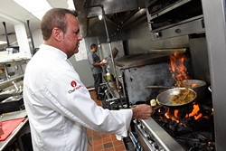 Meat Market Refectory co-owner and executive chef Steve Spitz sears off an entree in the kitchen. (Garett Fisbeck)