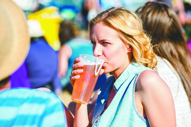 Young blond woman at summer music festival, drinking beer, sitting on the grass, crowded place - BIGSTOCK