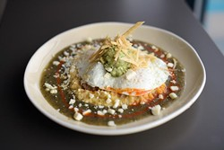 Chieftain's Revenge: spicy grits with tomatillo salsa, beer-braised pork, avocado salsa, fried eggs and Cotija cheese (Garett Fisbeck)