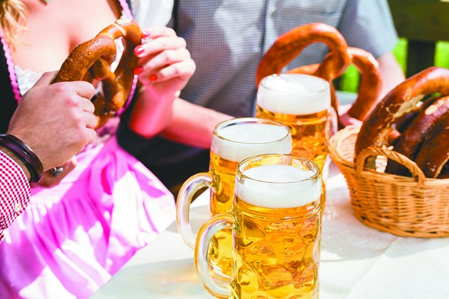 Glasses of beer and pretzel in German beer garden, close-up on the drinks and food - BIGSTOCK