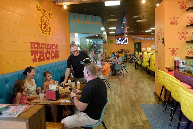 Manager Ron Sterling takes orders to a table at Hacienda Tacos