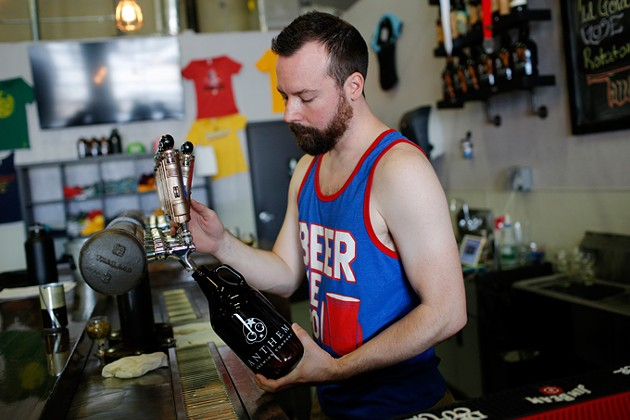 Ben Childers pours a growler of beer at Anthem Brewing Company in Oklahoma City, Tuesday, June 14, 2016. - GARETT FISBECK