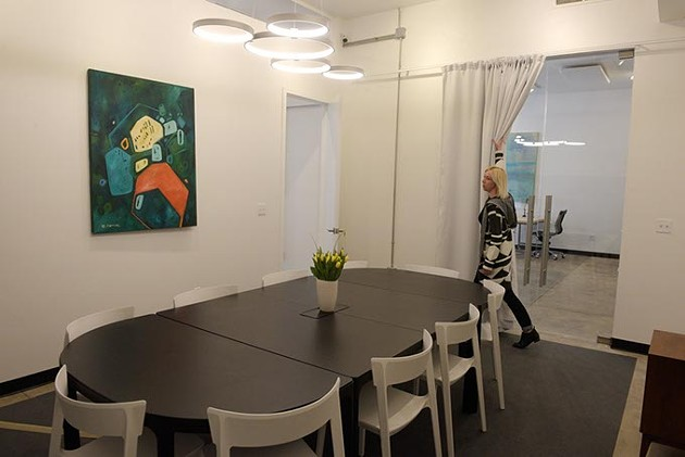Erin Cooper shows off the conference room at Halcyon Works in the Paseo District (Garett Fisbeck)