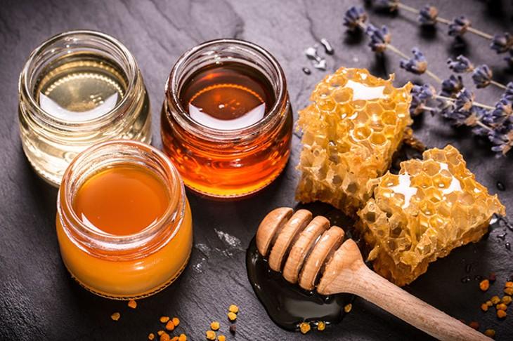 Honey in jar with honey dipper on black stone background - BIGSTOCK