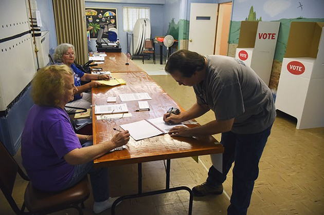 John Harrison signs in with election officals, from left, Eva Welch and Mary Austin, during the election on 7-14-15, at Crown Heights Church of the Nazarene.  mh