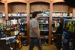An employee walks past beer selection at Poncho's Liquortown.  mh