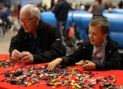 """Will Canipe, 8, from Wake Forest, assembles a """"car, boat, helicopter, submarine"""" alongside his grandfather, Giles Jeffreys, from Wendell, during the BrickUniverse Lego Convention at the Raleigh Convention Center on Sunday, March 29, 2015 in Raleigh, N.C. Canine said he plays with legos everyday """"except when I'm at Disney World and I'm at the beach."""" - AL DRAGO"""