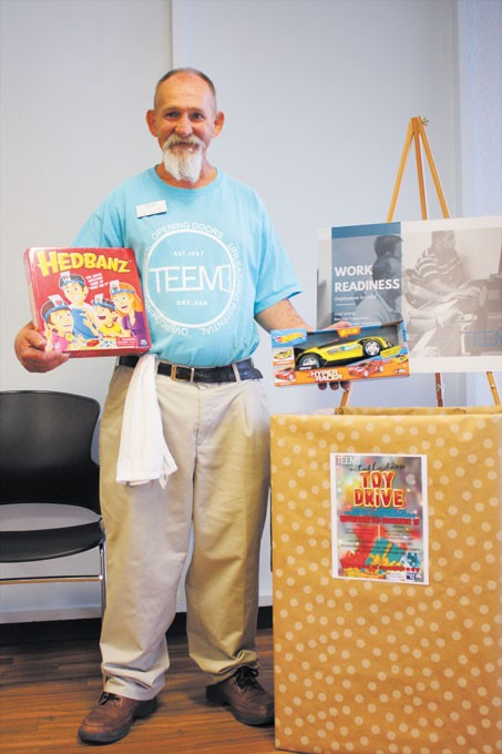 Tony Williamson, a former TEEM participant and now employee, holds two holiday gifts donated to be distributed to Oklahoma children who have a parent in prison this holiday season. | Photo Laura Eastes