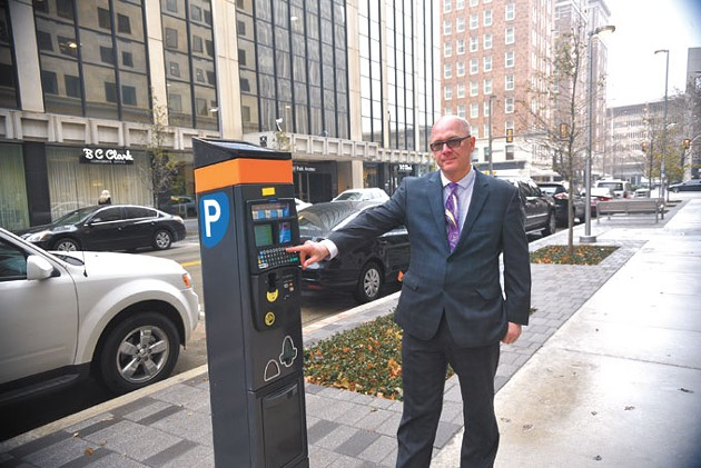 Cory Hubert stands next to a pay-by-plate parking kiosk along Park Avenue downtown. | Photo Laura Eastes