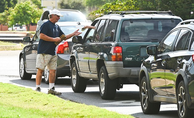 A man accepts cash from a driver after panhandling in a median in Oklahoma City in 2015. (Photo Gazette