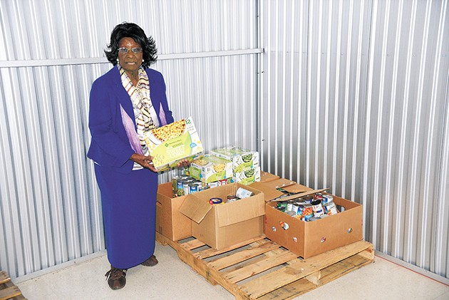 Sister Mable Stoss stands in one of three storage units that the Free Food Pantry and Educational Center uses to store donations. - LAURA EASTES