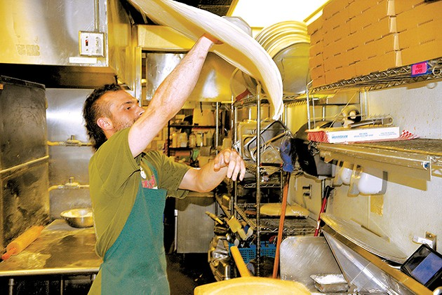 Matt Spivey tosses fresh pizza dough inside Falcone's Pizzeria. - JACOB THREADGILL