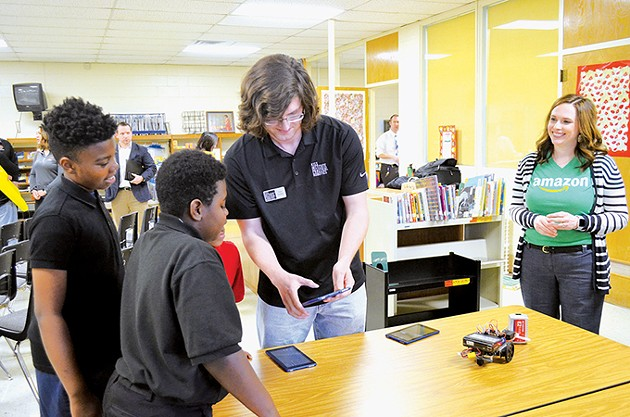 Tim Corbly shows three F.D. Moon Academy - students the programing features for Botball - robotics following a donation of six robotics kits - by Amazon to their school. - LAURA EASTES