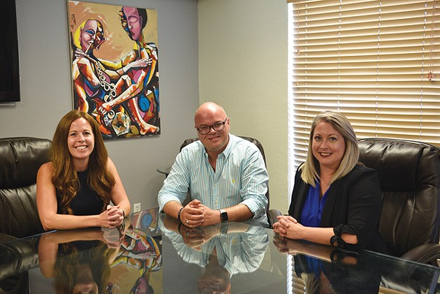 Women Lead Oklahoma's Kasey Greenhaw left and Lindsey Kanaly right sit in their shared conference room with Freedom Oklahoma - executive director Troy Stevenson center. The two organizations moved into a mutual office space in February. - BEN LUSCHEN