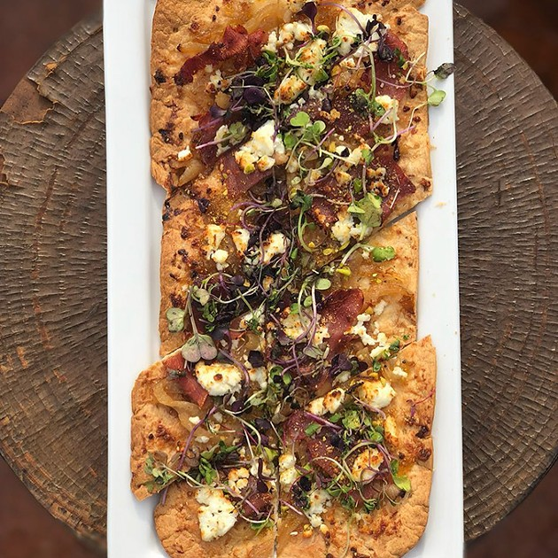 The Hipster flatbread features fig preserve, goat cheese, fresh prosciutto, caramelized onions, pistachios and microgreens. - PROVIDED
