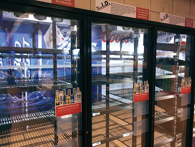 A beer cave at an OnCue Express on 36th Street and May Avenue sits nearly completely empty except for a flavored malt liquor on Monday Sept. 24. - JACOB THREADGILL