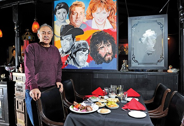 Jamil's owner Greg Gawey stands next to one of the restaurant's murals featuring famous Oklahomans. - GAZETTE / FILE