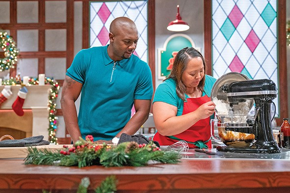 Christmas Cookie Challenge host Eddie Jackson observes Oklahoma cookie artist Lan McCabe pouring flour into a mixer. - FOOD NETWORK / PROVIDED