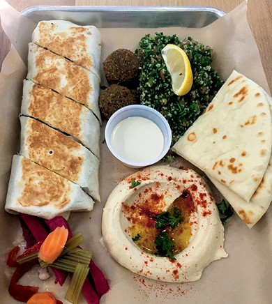 A shawarma wrap with falafel, tabbouleh, hummus, garlic sauce, pita bread and pickled vegetables - JACOB THREADGILL
