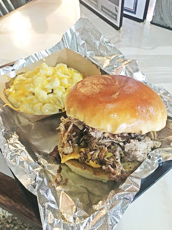 The Frank-N-Bill sandwich with smoked Angus - burger topped with pulled pork and a side of - seven-cheese mac - JACOB THREADGILL