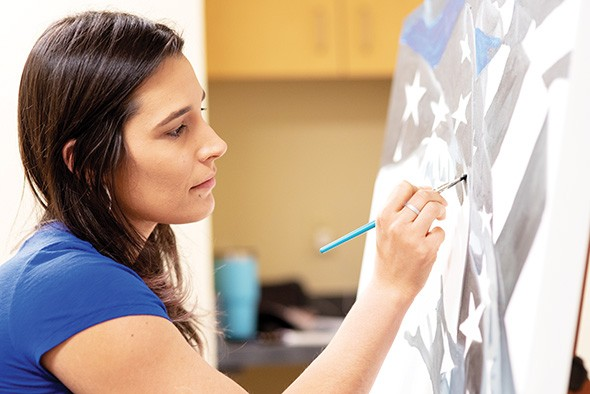 Erica Bonavida works on a painting of the police flag with the thin blue line for a local officer. - MIGUEL RIOS