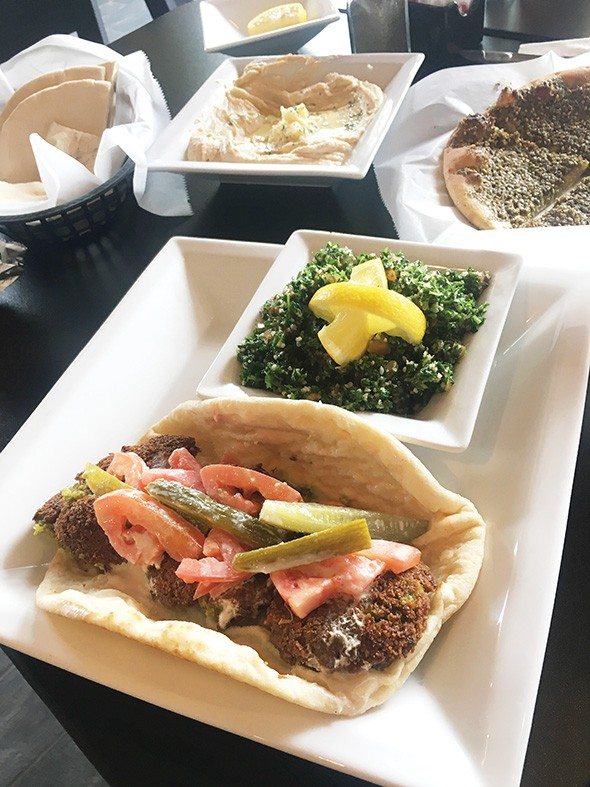 A falafel sandwich with a side of tabbouleh - JACOB THREADGILL