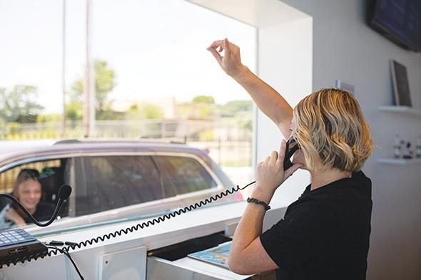 A budtender serves patients through a drive-thru at Stellar Herb. - ALEXA ACE